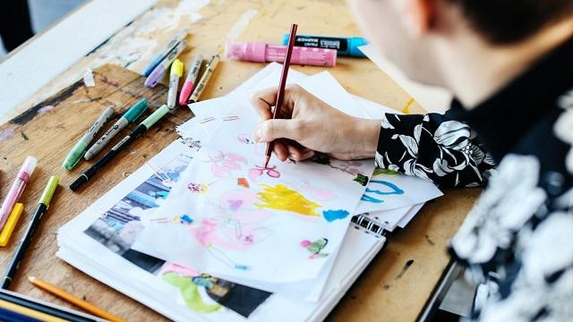 A person is making fashion sketches using colored pencils and felt pens.